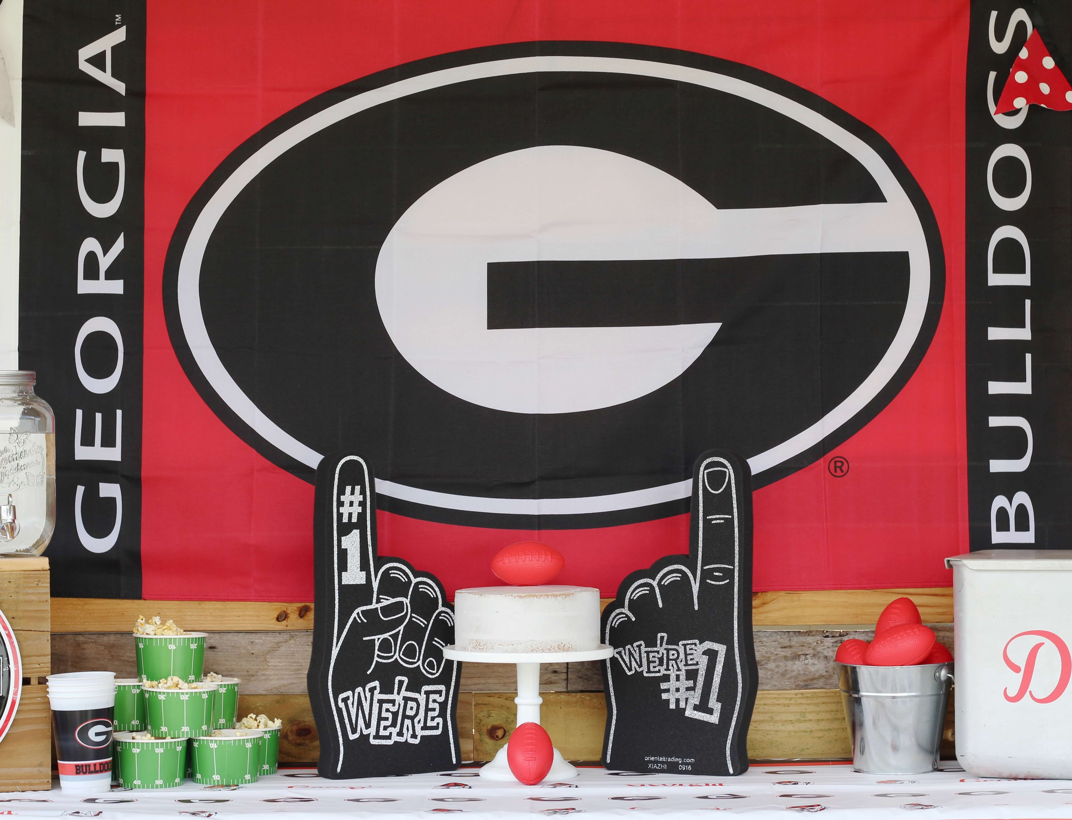 Check out this fantastic tailgate themed football party! Jessica, of Everyday Party Magazine, has a four sons that eat, drink and sleep sports. A football tailgate party was the perfect theme to kick off College Football Season! Father and sons are rabid Georgia Dawgs fans so the Dawgs starred at this party, but you could use a generic theme of football or substitute your family's favorite team and colors. From to the football-themed cake to the tailgate appropriate menu of party food, this party was a touchdown